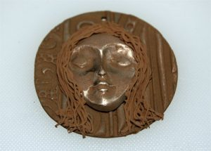 Dried bronze clay face pendant